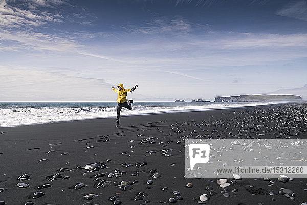 Reifer Mann springt vor Freude an einem Lavastrand in Island
