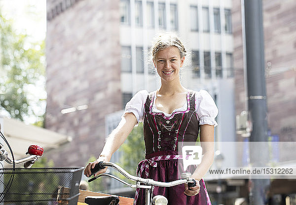 Portrait of smiling blond woman with bicycle wearing dirndl in the city  Freiburg  Germany