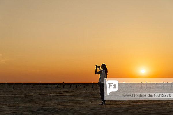Deutschland  Schleswig-Holstein  Sankt Peter-Ording  Frau beim Fotografieren am Strand bei Sonnenuntergang