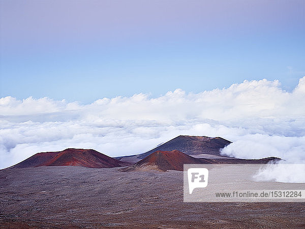 Idyllic view of Mauna Kea volcanic crater amidst clouds against blue sky