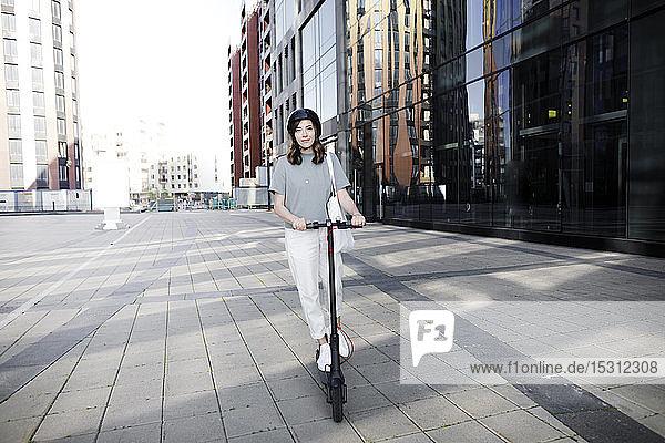 Frau mit E-Scooter und Helm  im Hintergrund moderne Bürogebäude