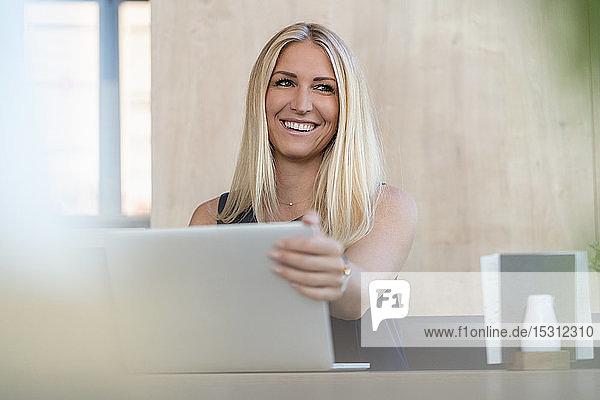 Porträt einer lächelnden blonden Geschäftsfrau mit Laptop in einem Café