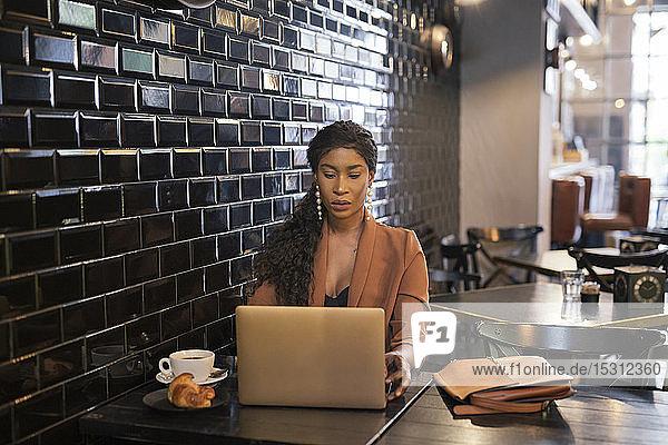 Schicke Geschäftsfrau mit Laptop am Tisch in einem Cafe