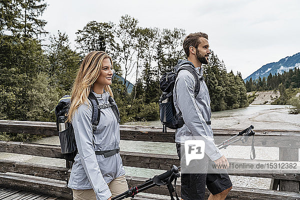 Confident young couple on a hiking trip walking on wooden bridge  Vorderriss  Bavaria  Germany