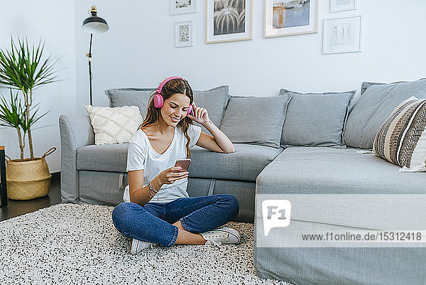 Lächelnde junge Frau sitzt auf dem Boden im Wohnzimmer und hört Musik mit ihrem Handy
