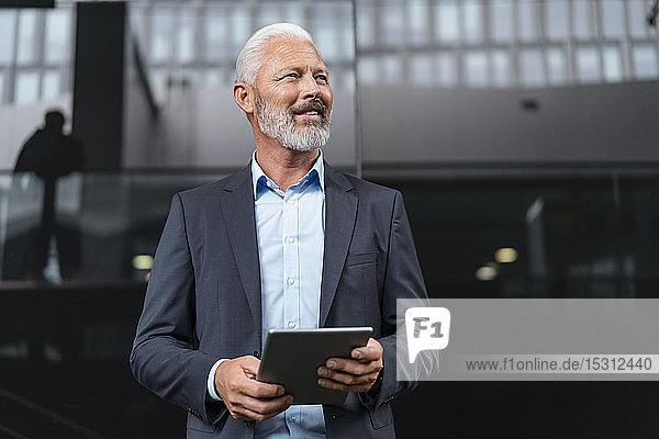Lächelnder reifer Geschäftsmann mit Tablette  der sich umsieht