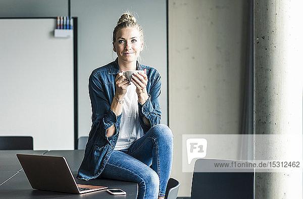 Portrait of businesswoman sitting on table in office having a coffee break