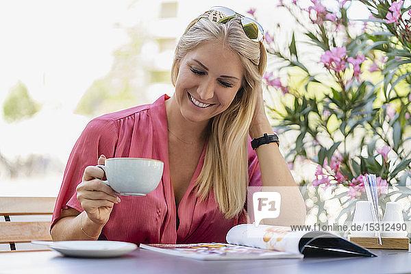 Porträt einer lächelnden blonden Frau  die im Straßencafé Kaffee trinkt und eine Zeitschrift liest