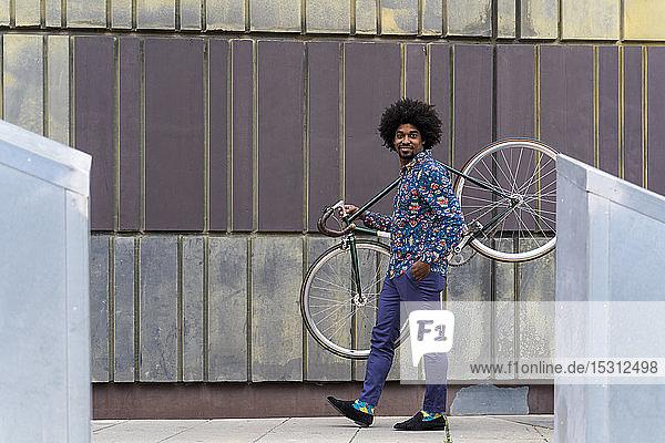 Stilvoller Mann mit Fahrrad in der Stadt
