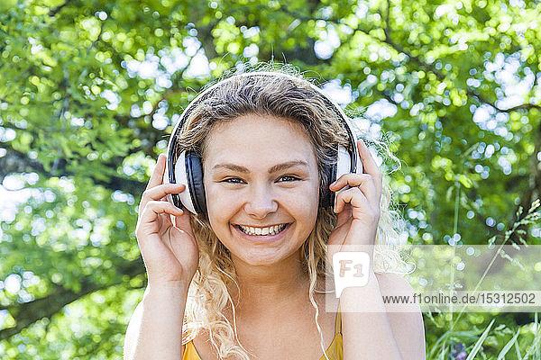 Lächelnde junge Frau  die Musik hört und in die Kamera schaut Lächelnde junge Frau, die Musik hört und in die Kamera schaut