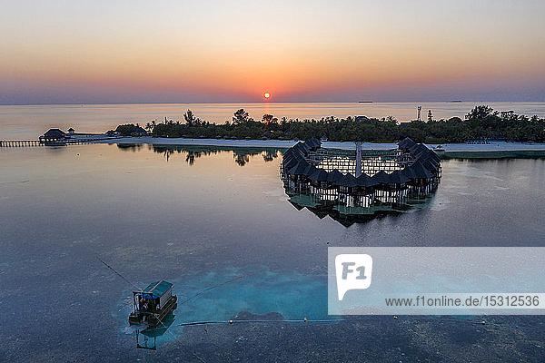 Malediven  Insel Olhuveli  Resort-Bungalows auf der Lagune des Süd Male Atolls bei Sonnenuntergang