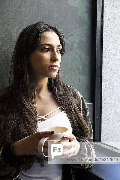Junge Frau sitzt mit einer Tasse Kaffee in einem Café und schaut zur Seite