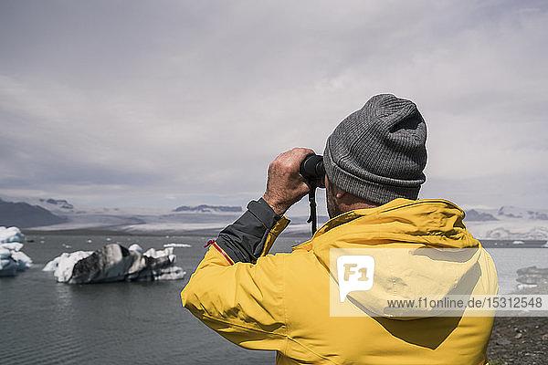 Erwachsener Mann beobachtet den Vatnajokull-Gletscher mit dem Fernglas  Island