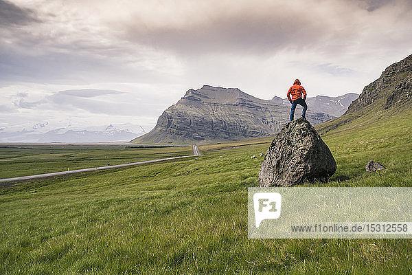 Auf einem Felsen stehender Mann in der südlichen Region  Island