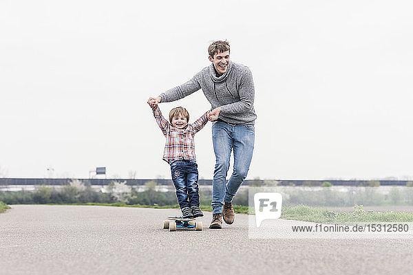 Vater und Sohn amüsieren sich  spielen mit dem Skateboard im Freien