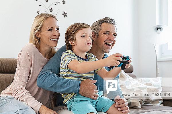 Glückliche Eltern mit Sohn spielen zu Hause auf der Couch Videospiele