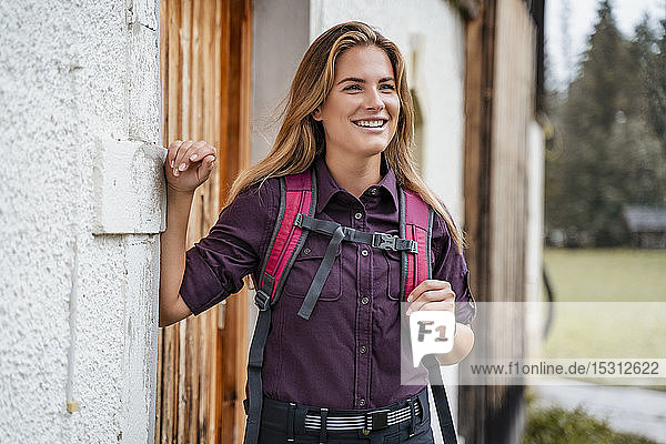 Smiling young woman at a farmhouse during a hiking trip  Vorderriss  Bavaria  Germany