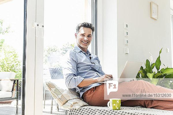 Reifer Mann sitzt auf dem Sofa und benutzt einen Laptop