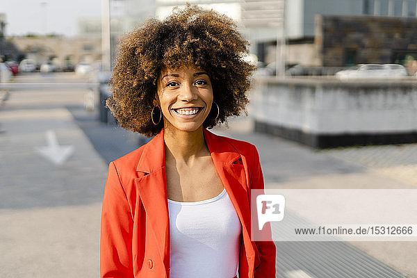Porträt einer lächelnden jungen Frau in rotem Anzugmantel