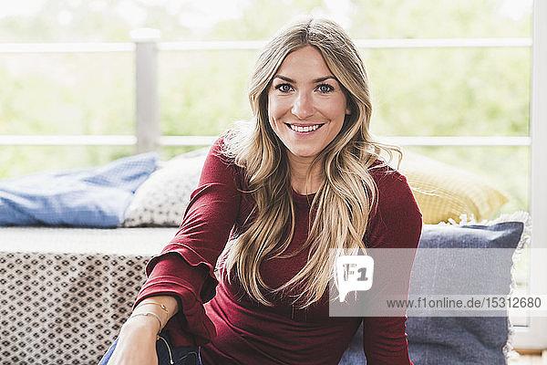 Porträt einer lächelnden blonden Frau  die sich zu Hause entspannt