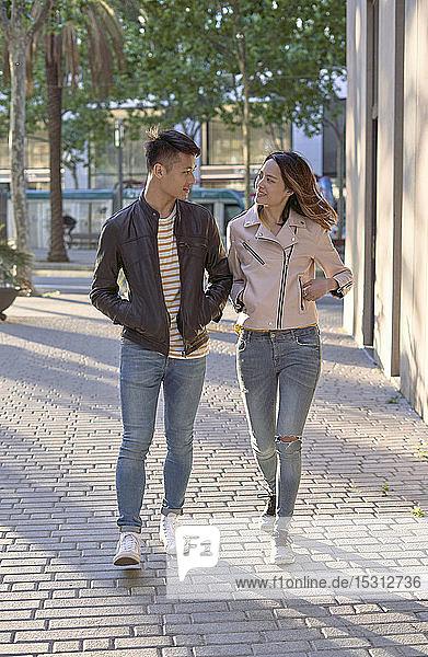 Ehepaar in Jeans und Lederjacken geht abends auf der Straße