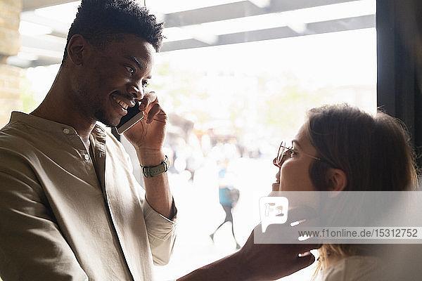 Porträt eines lächelnden jungen Mannes am Telefon  der seine Freundin berührt