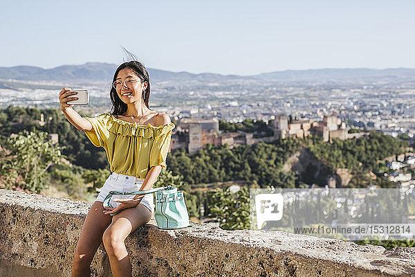 Lächelnde junge Frau beim Selfie in der Alhambra  Granada  Spanien