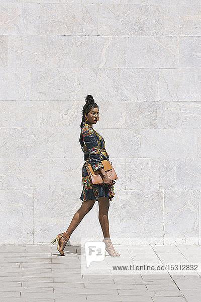 Porträt einer eleganten Frau in gemustertem Kleid  die im Freien spazieren geht