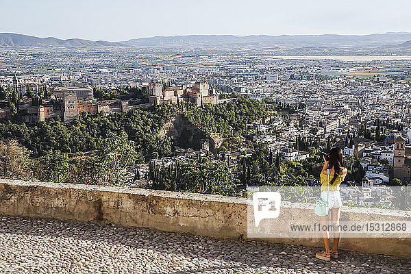 Young woman taking a picture at the Alhambra  Granada  Spain