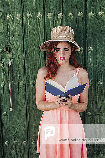 Portrait of redheaded young woman standing in front of green wooden door reading a book in summer