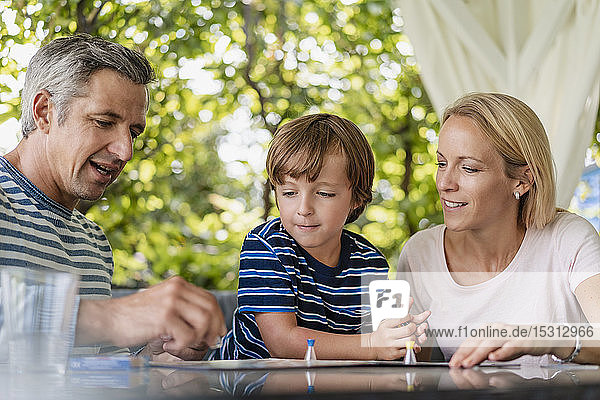 Happy parents and son playing a board game on terrace
