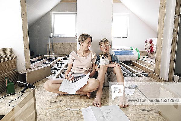 Glückliche Mutter mit Sohn in einem zu renovierenden Haus