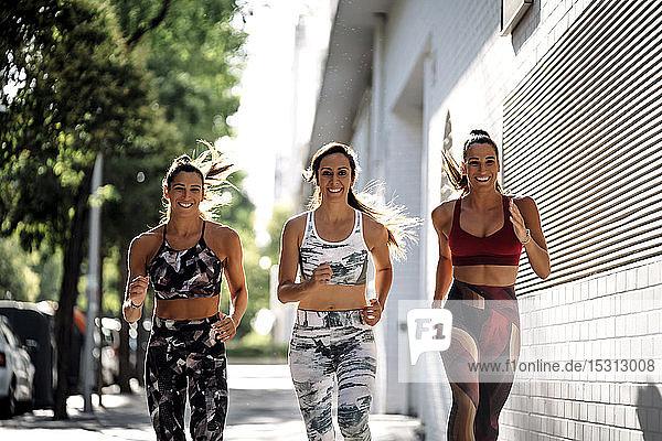 Drei glückliche  sportliche junge Frauen laufen in der Stadt