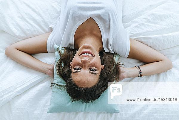 Draufsicht auf eine glückliche junge Frau  die im Bett liegt