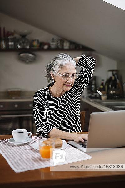 Portrait of senior woman using laptop at breakfast table