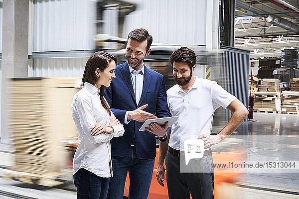 Lächelnder Geschäftsmann mit Tablette und Mitarbeiter im Gespräch in einer Fabrik