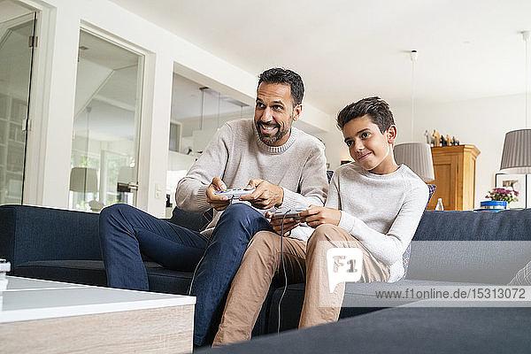 Glücklicher Vater und Sohn spielen Videospiel auf der Couch im Wohnzimmer