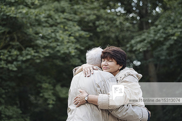 Portrait of senior woman hugging her husband in the woods