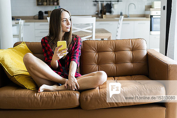 Young woman with cell phone on a couch at home