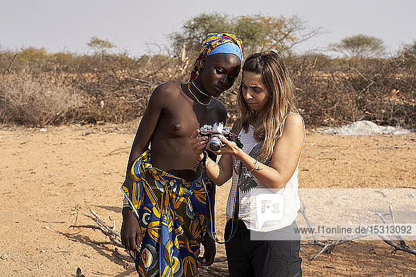 White woman showing her pictures to a mucubal woman  Tchitundo Hulo  Virei  Angola