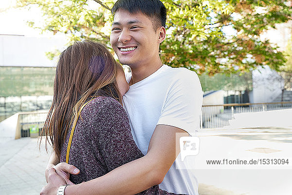 Happy young couple hugging outdoors