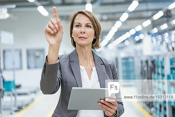Businesswoman with tablet in a modern factory touching virtual screen