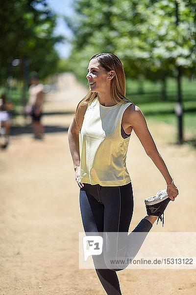 Lächelnde Frau streckt ihr Bein auf einem Weg in einem Park