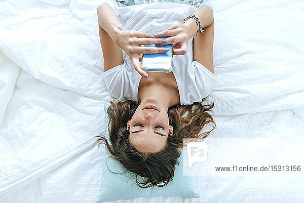 Draufsicht einer jungen Frau,  die mit ihrem Handy im Bett liegt