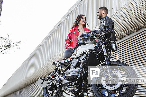 Couple with motorcycle helmets standing beside motorbike