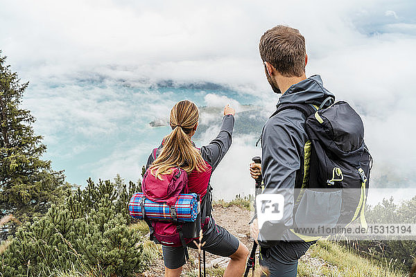 Young couple on a hiking trip in the mountains looking at view  Herzogstand  Bavaria  Germany