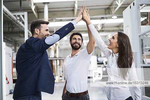 Happy businessman and employees high fiving in a factory