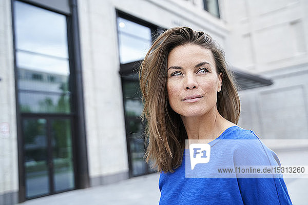 Portrait of attractive brunette woman wearing blue top in the city