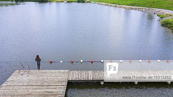 Luftaufnahme einer jungen Triathletin  die auf einem Steg an einem See steht