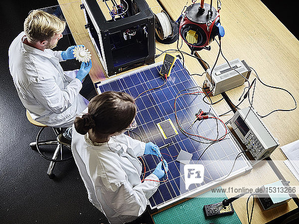Two technicians working on 3d printed turbine wheel and solar panel in lab